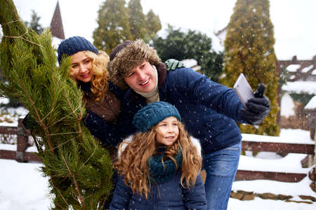 Beautiful mom, dad and daughter doing selfie with freshly cut christmas tree with smartphone near home. Young family Merry Christmas and Happy New Year preparation and celebration. Snow and winter.