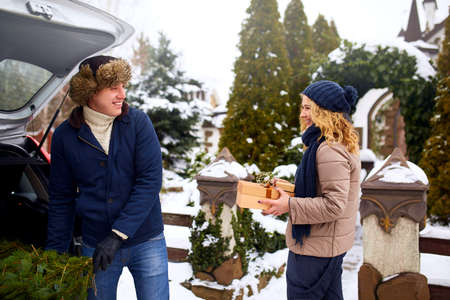 Couple unloading freshly cut down Christmas tree and gift boxes out of car trunk to decorate home. Happy man and woman prepare for New Year holidays together. Snowy winter weather outdoors. Stock Photo