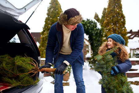 Smiling little girl and father get christmas tree out of car trunk near their house outdoors. Daughter helps dad with new year home decorations and fir-tree on snowy winter. Preparation for holidays. Stock Photo