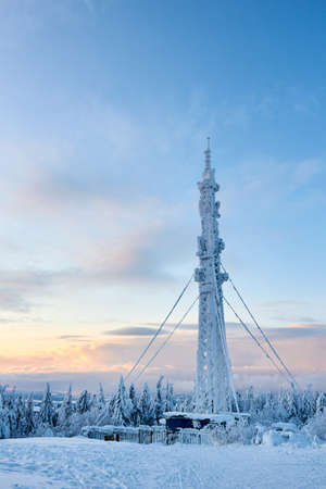 Icy cellular base station antenna covered with snow. Cell site tower on moutain hill. Telephone network transceivers and communication equipment on frosty weather day after snowstorm. Blue sky. Stock Photo