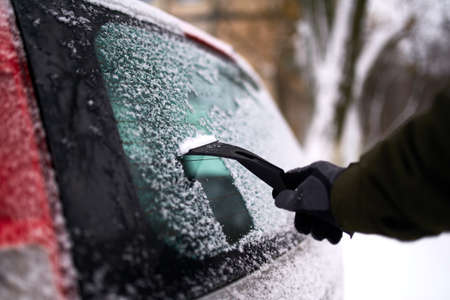 Cleaning the rear car window of snow with ice scraper before the trip. Man removes ice from car rear window wiper. Male hand cleans car with special tool at snowy winter day.