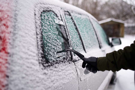 Cleaning the side car windows of snow with ice scraper before the trip. Man removes ice from car windows. Male hand cleans car with special tool at snowy frosty winter day.
