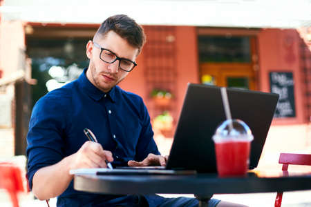 Freelancer man hand writing on paper notebook near his laptop in outdoor cafe. Young businessman in glasses taking notes in notepad with stylish pen. Student working on laptop. Stock Photo