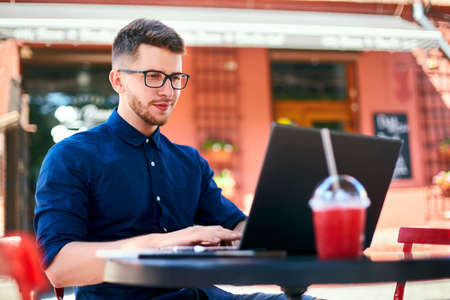 Young attractive hipster freelancer working remotely on laptop at outdoor cafe. Businessman browsing internet at coffeshop. Blogger posts to social media on travel using 5g internet. Telecommuting. Stock Photo