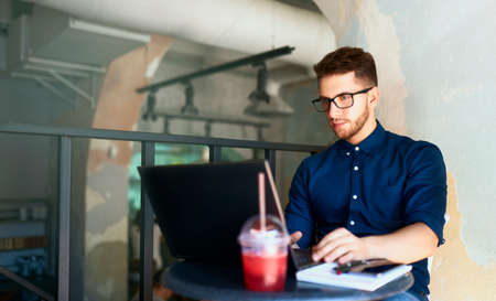 Young attractive hipster freelancer working remotely on laptop in loft cafe. Businessman browsing internet at coffeshop. Blogger posts to social media on travel using 5g internet. Telecommuting theme.