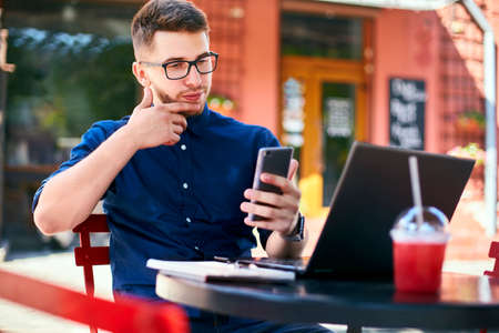Thoughtful young businessman holding modern smartphone. Freelancer with a mobile phone thinks about reply. Man in glasses with laptop on table in outdoor cafe. Multitasking and telecommuting theme.