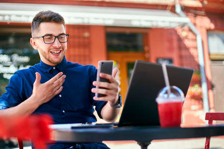 Smiling freelancer with smartphone telecommuting via online video chat. Distracted from work businessman holding mobile phone. Man in glasses with laptop on table in outdoor cafe. Multitasking theme. Stock Photo