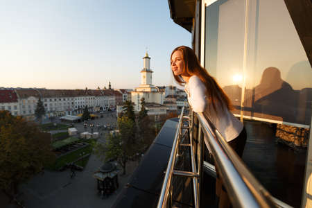 Young beautiful woman admiring panoramic view of european street architecture high from the balcony. Girl looking at street panorama on sunset.