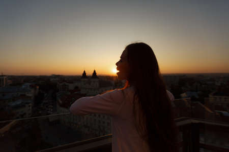 Young beautiful woman admiring panoramic view of european street architecture high from the balcony. Girl looking at street panorama on sunset. Happy female have fun eating a sun.