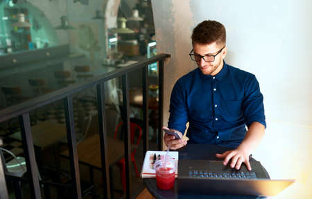 Freelancer typing text on smartphone and working remotely. Hipster holding mobile phone and writing message. Smiling young businessman in glasses telecommuting with cellphone on laptop in loft cafe. Stock Photo