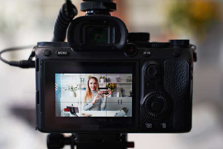 Display of camera recording video blog for blonde beauty blogger woman with make-up at home studio. Influencer vlogger girl live streaming cosmetics masterclass. Online learning and marketing concept.