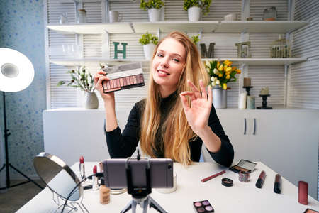 Beauty blogger woman filming daily make-up routine tutorial near camera on tripod. Influencer girl live streaming cosmetics product review in home studio. Vlogger female showing eye shadow palette.
