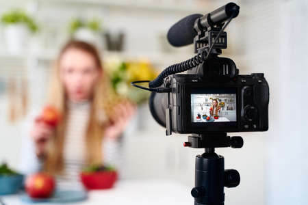 Display of camera recording video blog for food blogger woman with apple, pineapple in kitchen studio talking about healthy vegan eating. Influencer vlogger girl live streaming nutrition masterclass.