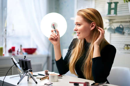 Vlogger female applies lipstick on lips. Beauty blogger woman filming daily make-up routine tutorial at camera on tripod. Influencer blonde girl live streaming cosmetics product review in home studio