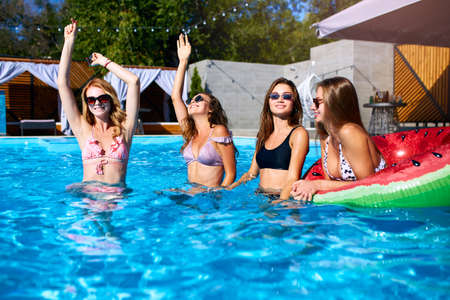 Beautiful hot pretty girls in bikini have pool party dancing with inflatable watermelon swim ring floaty. Attractive slim women in swimsuits and sunglasses have fun relaxing on sunny summer day.