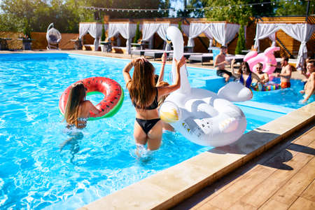 Hot pretty girls in bikini walking together with inflatable swan, swim ring into swimming pool. Attractive slim women in swimsuits have fun relaxing on sunny day summer party at luxury resort, villa.