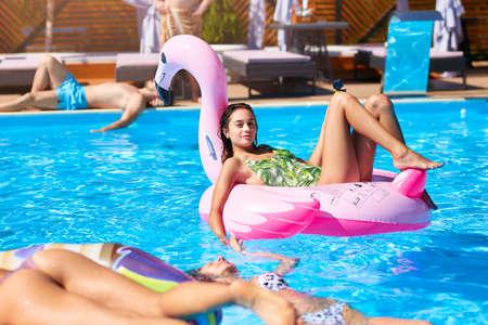 Młoda gorąca dziewczyna w bikini relaks i chłodzenie na pływak nadmuchiwany różowy flaming. Dość opalona kobieta w stroju kąpielowym leży w słońcu na tropikalnych wakacjach. Dość kobiece opalanie w luksusowym kurorcie. Zdjęcie Seryjne