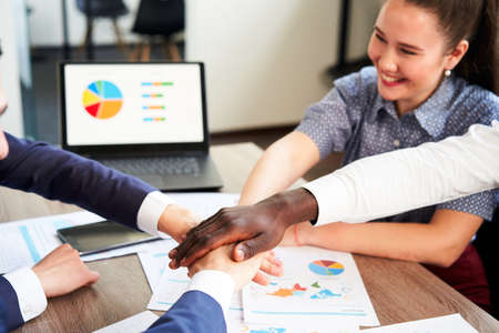 International business team showing unity with their hands stacked together in pile. Black african-american hand on top. Mixed race multiethnic group join their hands. Businessman and businesswoman.