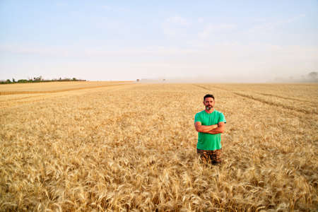 Happy farmer proudly standing in wheat field with arms crossed on chest. Agronomist wearing corporate uniform, looking at camera on farmland. Rich harvest of cultivated cereal crop. Harvesting season. Фото со стока