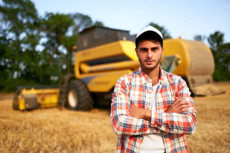 Portrait of proud harvester machine driver with hands crossed on chest. Farmer standing at his combine. Agronomist looking at camera. Rancher at harvesting work on stubble of harvested wheat field.