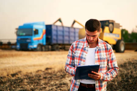 Farmer controls loading wheat from harvester to grain truck. Driver holding clipboard, keeping notes, cargo counting. Forwarder fills in consignment waybills. Agricultural commodities logistics. 版權商用圖片
