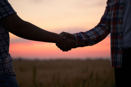 Farmer and agronomist silhouettes shaking hands standing in a wheat field after agreement in dusk. Agriculture business contract concept. Combine harvester driver and rancher handshake. Negotiations.