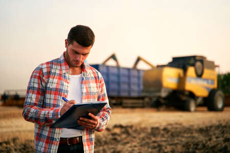 Farmer controls loading wheat from harvester to grain truck. Driver holding clipboard, keeping notes, cargo counting. Forwarder fills in consignment waybills. Agricultural commodities logistics. Фото со стока