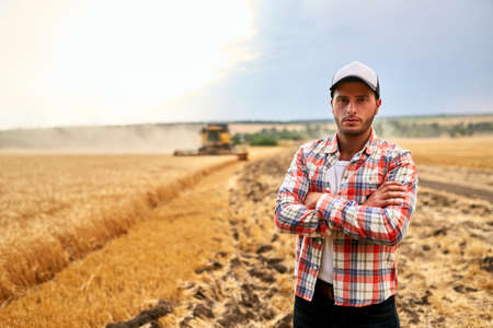 Happy farmer proudly standing in a field with arms crossed on chest. Combine harvester crop rich wheat harvest on background. Agronomist wearing flannel shirt, looking at camera on a farmland.