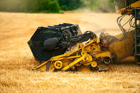 Cutting bar unit or reaper machine cuts stems. Combine harvester working in wheat field. Harvesting machine driver cutting crop in a farmland. Agriculture theme, harvesting season. 版權商用圖片