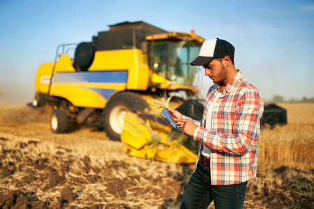 Precision farming. Farmer holding tablet for combine harvester guidance and control with modern automation system. Agronomist using online data management software generating yield maps at wheat field