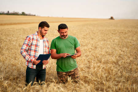 Two farmers stand in wheat stubble field, discuss harvest, crops. Senior agronomist with touch tablet pc teaches young coworker. Innovative tech. Precision farming with online data management soft.