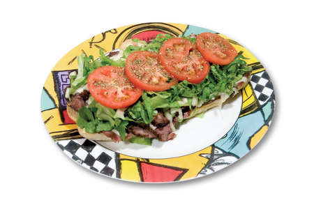 Sub sandwich with fried meat, lettuce, tomatoes and cheese on a white background