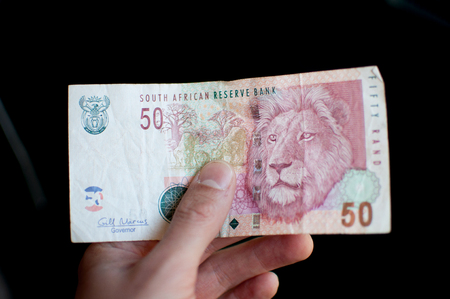 emerging markets: Hand holding a fifty 50 rand currency note south african africa money Stock Photo