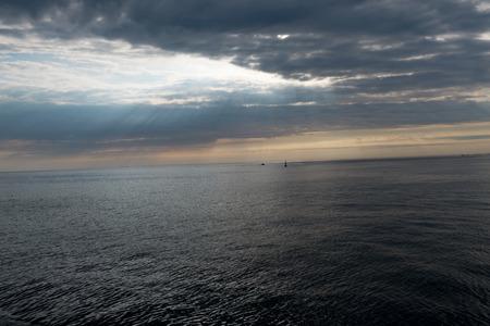 Sunbeams pierce through clouds in salem harbor on the atlantic ocean