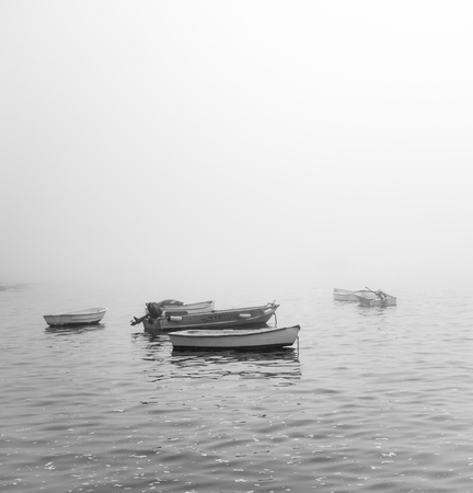 Row boats in foggy ocean in Marblehead massachusetts haze black and white Stock Photo