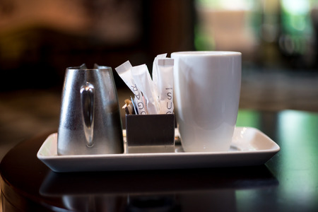 Sugar packets cream and coffee on tray for breakfast Stock Photo