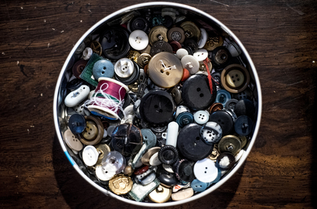 tin of old buttons and thred background vintage messy Stock Photo