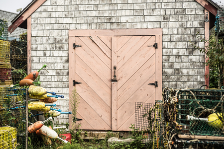 lobster traps and nets at fishing shed with salmon colored pink door