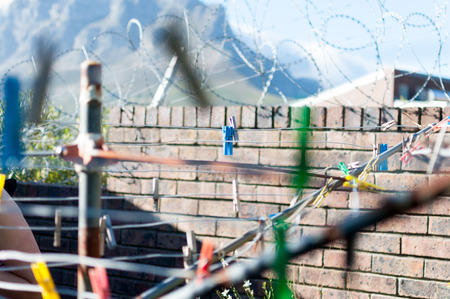 Barbwire wall for security at prison and clothesline clothes pins Stock Photo