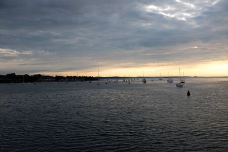 Sunrise in salem harbor Massachusetts sailboats moored ocean