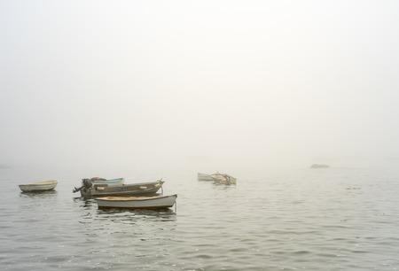 Row boats in foggy ocean in Marblehead massachusetts haze Stock Photo