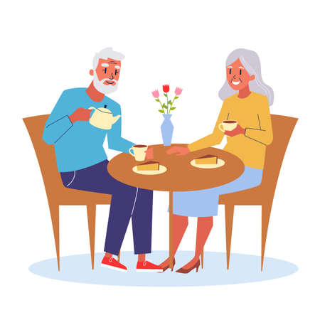 Happy old couple sitting at the table and drink tea