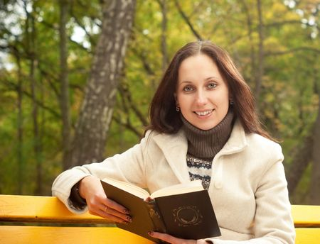 smilling: young smilling woman sitting on bench with book Stock Photo