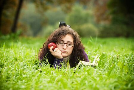woman lays on a grass and reads the book photo