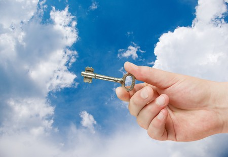 retro key in hand on blue sky background photo