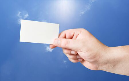 Blank paper card in human hand on blue sky background Stock Photo - 8035367