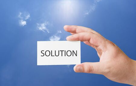 solution text on white card in human hand Stock Photo