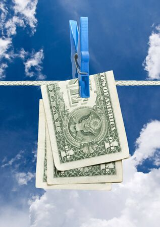 u.s. dollar on rope with clothespin over blue sky photo