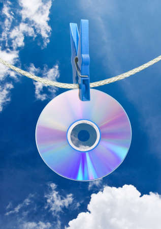 cd on rope with clothes pin over blue sky photo