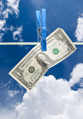 U.S. dollar on rope over blue sky background photo